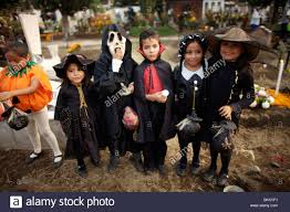 girls and boys dressed in halloween costumes visit the cemetery in