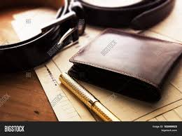 documents pen belt and a leather wallet on a wooden desk hotel