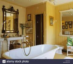 antique mirror above basin in yellow bathroom with brass shower