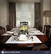 white placemats and plates in modern grey dining room with white