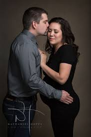 Maternity photo of husband kissing wife on the temple