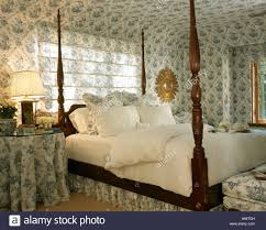 four poster bed with white linen in country bedroom with blue and