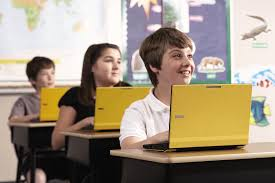 children in classroom with laptops