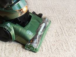 a green vacuum cleaner sweeping the carpet stock photo picture