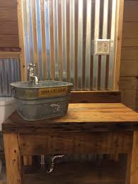 corrugated tin walls with cypress vanity and galvanized bucket