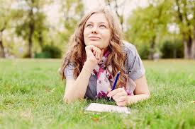 Teenage girl wearing checkered shirt and scarf lying down on grass in autumn park with notebook