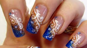 glittery blue and copper tips white swirls and rhinestones design