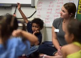 YMCA staffer Courtney Baeyen sits with Tawon George in a kindergarten class at L C  Elementary School Pioneer Press
