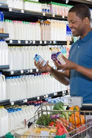 Photo of a man reading cartons in a grocery store