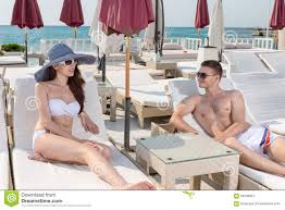 Luxury Beach Chair Couple Relaxing On Lounge Chairs At Beach Resort Stock Photo