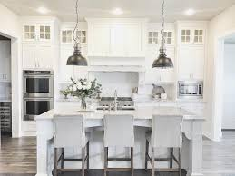 gray and white kitchen with metal pendant lamps over large marble