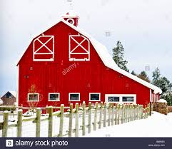 Gambrel Roof A Red Barn With A Gambrel Roof And Wooden Fence Line Surrounded By