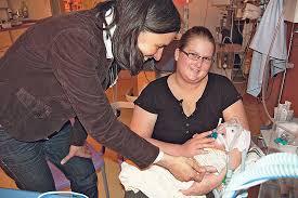 Christine Randelhoff besucht eine Mutter mit ihrem Frühchen. Der Junge wog bei der Geburt nur 460 Gramm. Foto: Heike Sieg-Hövelmann