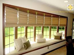 the bay window with seat in living room and horizontal blinds on