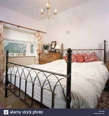 black cast iron bed with red cushions and white bedlinen in small