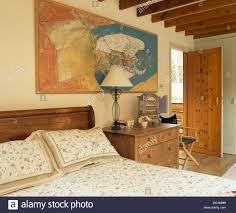 large painting above bed with floral bedlinen in beamed country