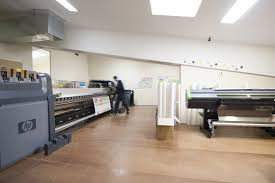 the wall sticker company is an australian award winning business an office with large printers and a man operating one telstra award winner the wall sticker company