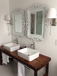 white bathroom with vessel sinks and wood table as vanity like the
