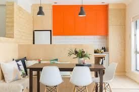 Cream Subway Tile Backsplash by Cream Banquette Scandinavian White Dining Chair Orange Cabinets