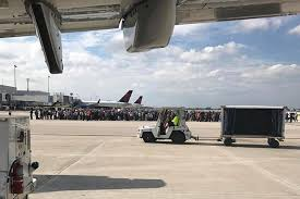 Photo courtesy of Taylor Elenburg shows Passengers gathering on the tarmac of the Fort Lauderdale