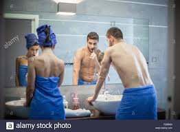 rear view of young couple brushing teeth in bathroom mirror stock