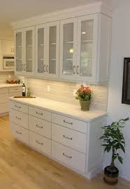 White Shaker Kitchen Cabinet Doors Woman Standing In Tall Aisle Kitchen With White Brick Wall White