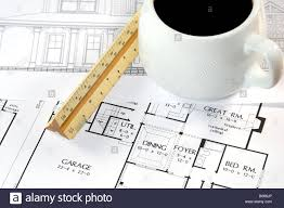 home design drawings and a coffee on an architects desk stock home design drawings and a coffee on an architects desk