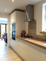 would love one entire wall of tall units like this plus full howdens white gloss intergrated kitchen with solid oak full stave worktops wood effect porcelain