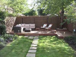 small modern backyard garden with green grass and footpath plus