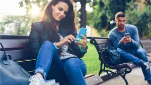 Couple on park benches on smartphones BBC