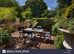 Outdoor Seating by Formal Outdoor Seating Area With Large Urns Stone Table And Brick