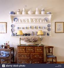 blue and white china displayed on a shelf in a traditional dining